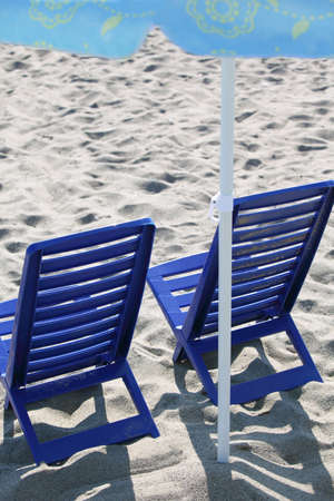 window shade: Two dark blue plastic chairs stand on  beach under  umbrella