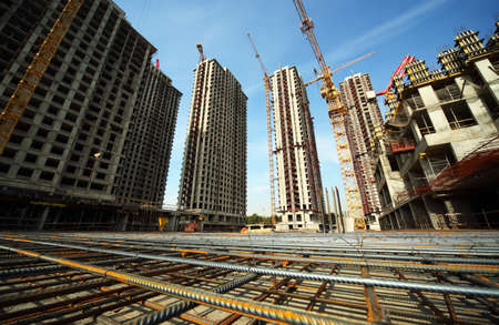 high rise buildings: Between tall buildings under construction and cranes under a blue sky