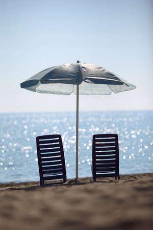 ashore: Near  sea ashore two dark blue plastic chairs stay under  large umbrella