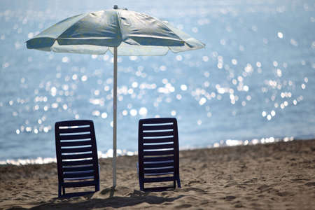 Two dark blue empty chairs  stand on  beach near  sea under shade of large umbrella photo