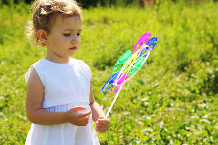 The little girl with the motley pinwheel standing in the grass photo