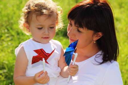 keeps: Mother keeps the little girl with two colorful pinwheels