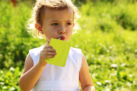 The little girl standing in the grass and drinking a juice photo