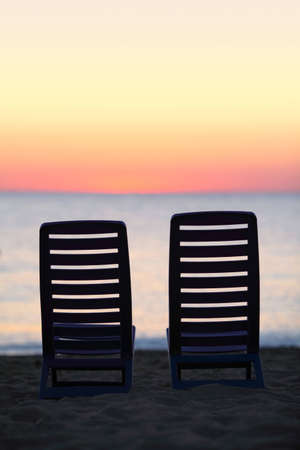 mandatoriccio: Two empty chairs stand on sand near  sea  during sunset Stock Photo