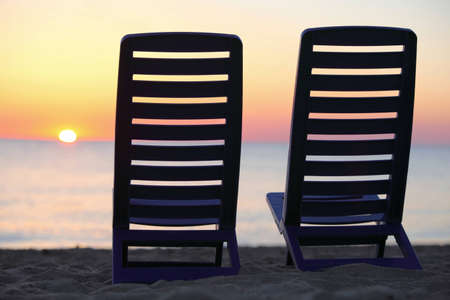 Two plastic chairs stand on  beach near water with  view on sunset photo