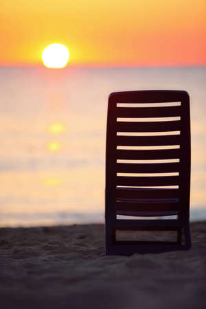 Dark blue plastic chair stands on  beach near  sea during sunset photo