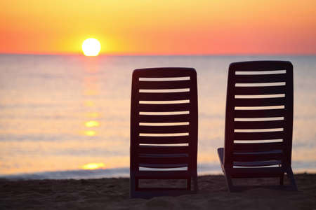 Two empty dark blue chairs stand on  beach in  evening with  view on marine sunset photo