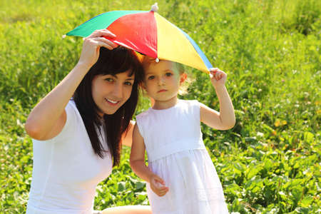 sun umbrella: Mother and daughter hide under an umbrella from the sun Stock Photo