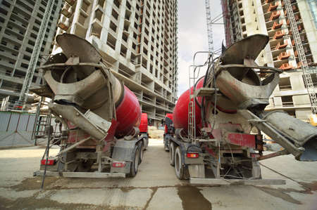 reach truck: Two concrete mixer stand near unfinished tall high-rise buildings