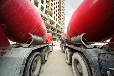 reach truck: Between two concrete mixer standing near unfinished tall high-rise buildings