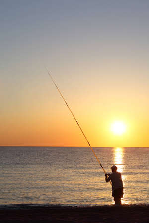 exterminating: Fisherman stands ashore exterminating with  large fishing-rod and threads  bait