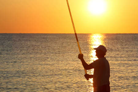 ashore: Man stands ashore with  fishing-rod and fishes on sunset