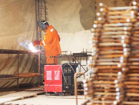 grate: Lavoratore in grigliati metallici saldati arancione vestiti di lampada ad acetilene