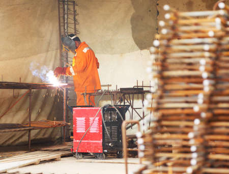 Worker in orange clothes weld metal gratings by acetylene torch