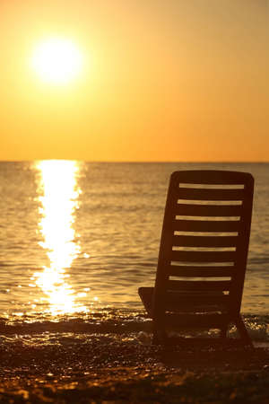 Empty chair stands sideways on  sea-shore in the evening during sunset photo
