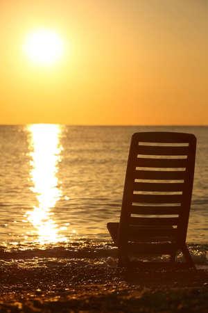 sedia vuota: Sedia vuota si trova di traverso sulla riva del mare di sera durante il tramonto
