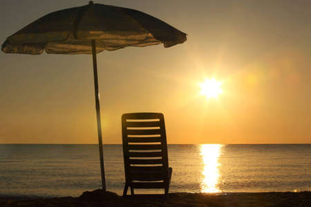 One plastic chair stands on  beach under  opened umbrella on sunset photo