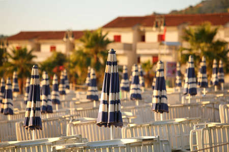 mandatoriccio: Deck-chairs and beach umbrellas neatly built rows on  beach in  morning next to cottages, shallow depth of focus