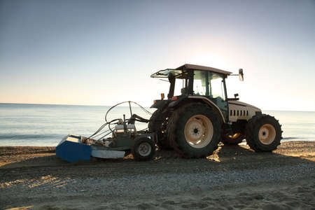 openly: Tractor with  trailer in  morning takes garbage away on  beach