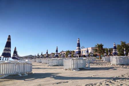 mandatoriccio: sun lounger with umbrellas are neatly built rows in  morning on  beach