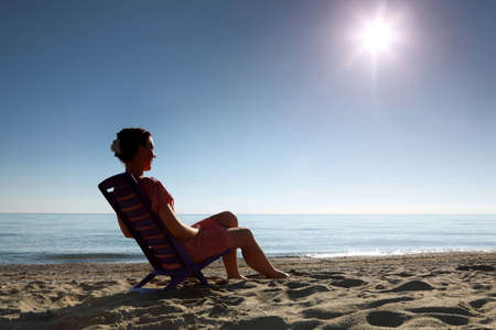Woman sits on  dark blue plastic chair sideways and becomes tanned in  morning on  beach photo