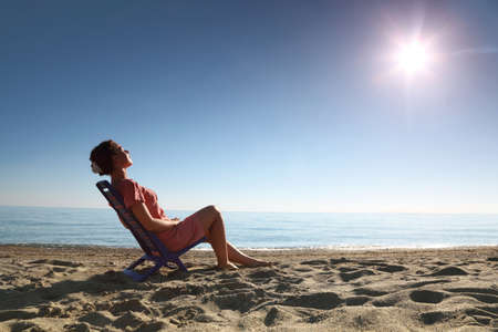 Woman sits on  plastic chair on  sea-shore by  person to  sun and becomes tanned, heaving up  head photo