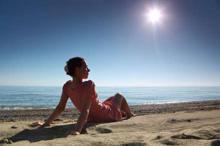 Woman in  morning sits on sand leaning against hands near  sea and becomes tanned