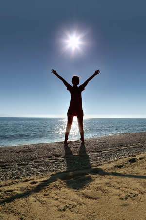 heaving: Woman stands on toes ashore  opposite  sun , heaving up hands upstairs