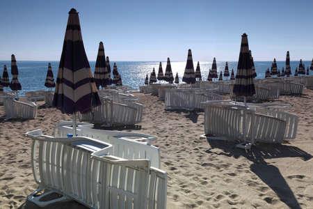 Sun lounger neatly built near closed beach umbrellas in  morning on sand