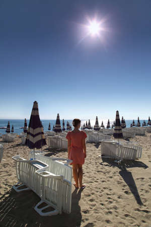 mandatoriccio: Woman stands on sunny beach with sun loungers and umbrellas
