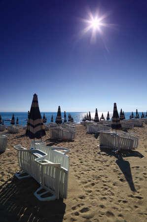 mandatoriccio: Empty sandy beach with folded umbrellas and sunbeds, burning sun and cloudless sky