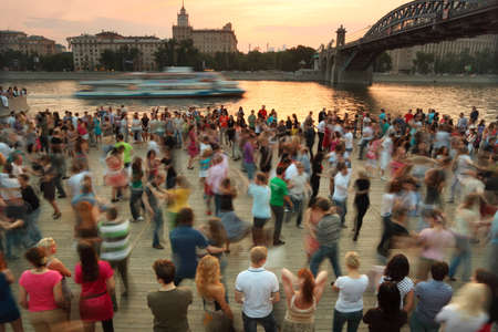 square dancing: MOSCOW - MAY 15: People dance on Frunzenskaya embankment near bridge, Petrovsky park organisation, motor ship on river May 15, 2010 in Moscow, Russia Editorial