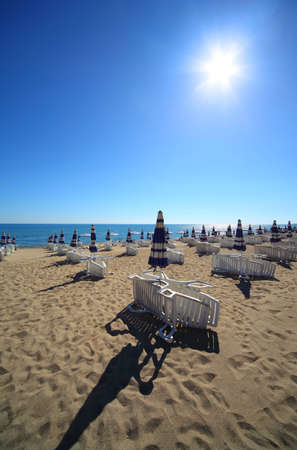 mandatoriccio: Empty sandy beach with folded and open umbrellas and sunbeds, burning sun and cloudless sky