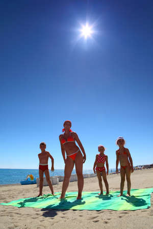 Mother and her children, son and two daughters, standing on the green coverlet on a sandy beach and doing gymnastics photo