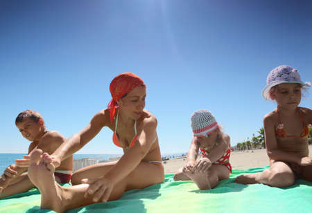 coverlet: Mother and her children, son and two daughters, sitting on the green coverlet on a sandy beach and doing gymnastics