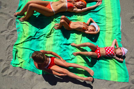 Mother and her children, son and two daughters, lying on the green coverlet on a sandy beach and doing gymnastics
