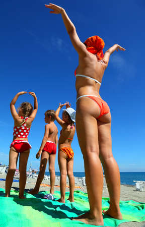 Mother and her children, son and two daughters, standing back on the green coverlet on a sandy beach and doing gymnastics