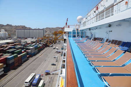 big cruise ship in port in right side of image. embarkation. many cargos in left.