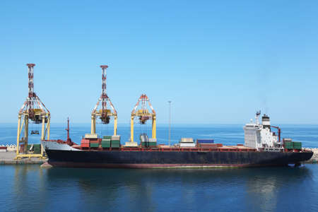 big merchant ship with cargos on a board at its moorings in port.