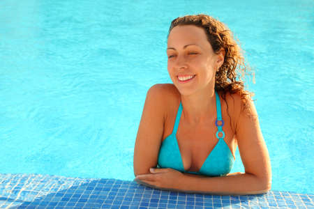 mandatoriccio: Smiling girl in blue bikini with brown curly hair stands in swimming-pool and looks in direction