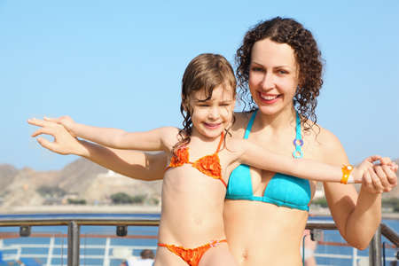 smiling beautiful woman with her daughter on deck of cruise ship. photo