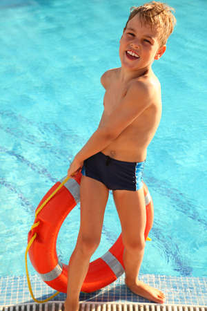 Cheerful little boy pulls out red buoy from the swimming-pool Stock Photo - 12614568