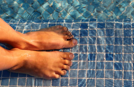 bare feet boys: Small boy feet are jointed and putted in water of blue swimming-pool Stock Photo