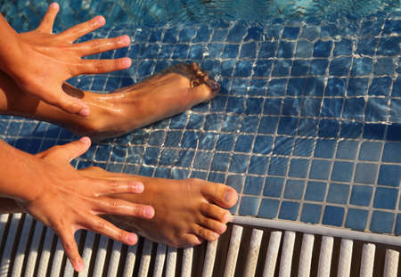 foots: Splayed fingers and toes are putted in water of swimming-pool
