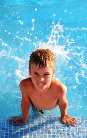 boys only: Little smiling boy splash around in water in blue swimming-pool