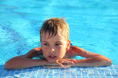 mandatoriccio: Little boy lies in swimming-pool and thoughtfully looks sideways