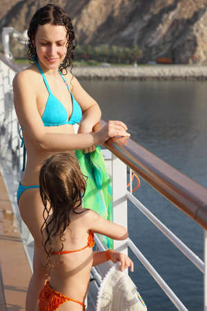 persian gulf: beautiful woman with her daughter both wearing swimming suit are standing on deck of cruise ship