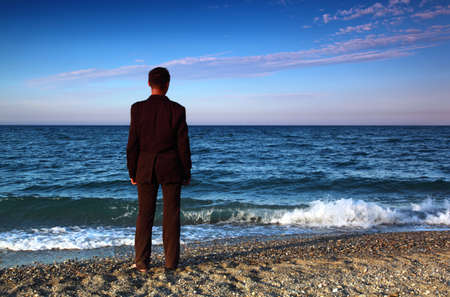 recreate: Barefooted man in suit stands back on stone coast at evening