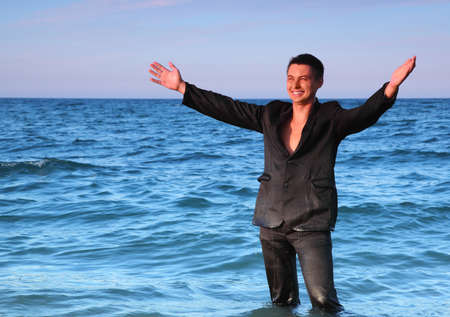 Smiling man in suit stands in sea and open hands at evening photo