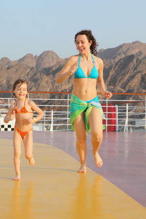 joyful woman with her daughter are running on deck of cruise ship photo